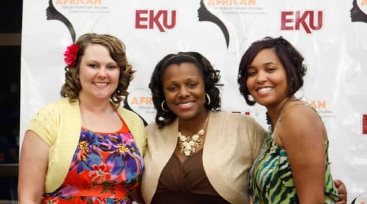 Three women standing in front of EKU backdrop